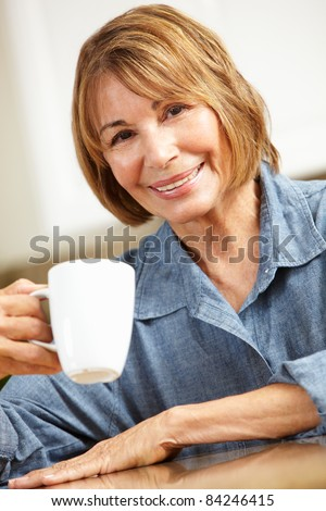 Mid age woman drinking coffee - stock photo