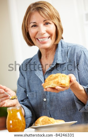 Mid age woman eating croissants - stock photo