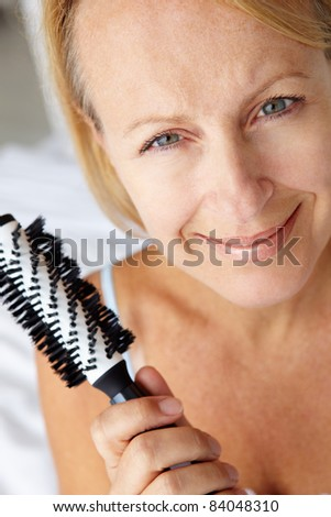 Mid age woman holding hairbrush - stock photo