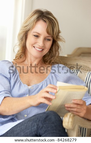 Mid age woman reading a book - stock photo
