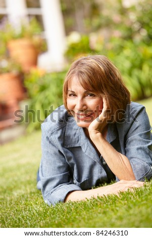 Mid age woman relaxing in garden - stock photo