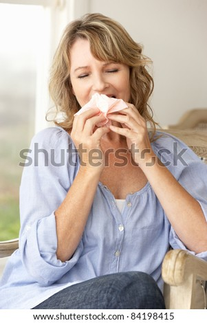 Mid age woman sneezing - stock photo