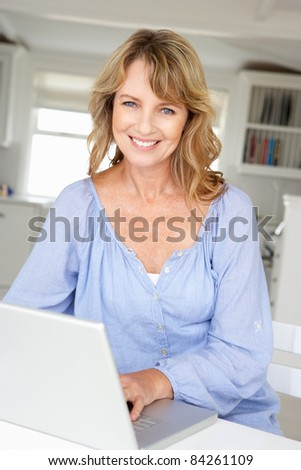 Mid age woman using laptop - stock photo