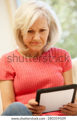 Mid age woman using tablet at home - stock photo