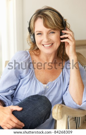 Mid age woman wearing headphones - stock photo