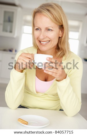 Mid age woman with coffee at home - stock photo