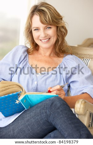 Mid age woman writing in notebook - stock photo