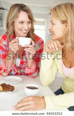Mid age women chatting over coffee at home - stock photo