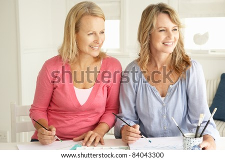 Mid age women painting with watercolors - stock photo