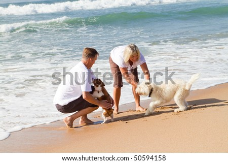 mid-aged couple playing with family dog on beach - stock photo
