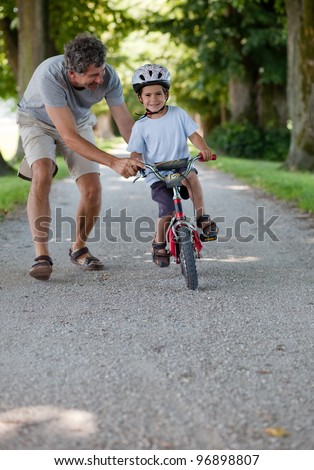 Mid aged man teaching his son to ride a bicycle - stock photo