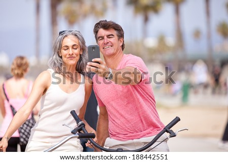 Mid Couple on vacation taking a selfie while riding Bikes - stock photo
