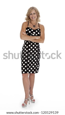 Mid-forties woman standing on white background wearing polka-dot dress with arms crossed - stock photo