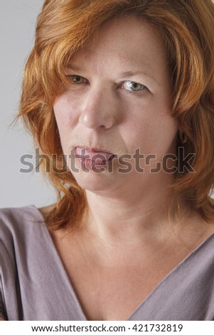 mid-forties woman with red hair, showing her tongue in annoyance