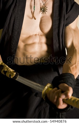 mid section af a martial arts guy wit samurai sword or katana. showing incredible stomach muscles, chest and bicep - stock photo