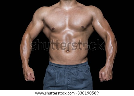 Mid section of a bodybuilder man against black background