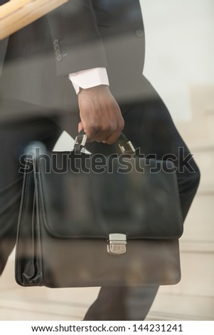 Mid section of a business person carrying a briefcase up the stairs