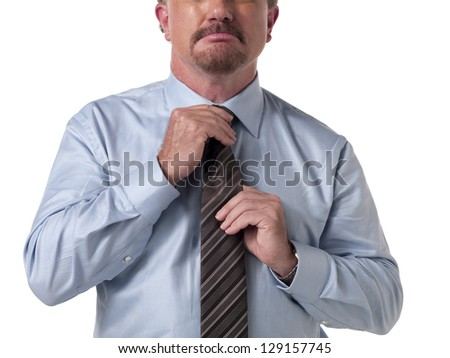 Mid section of a businessman adjusting his necktie over white background