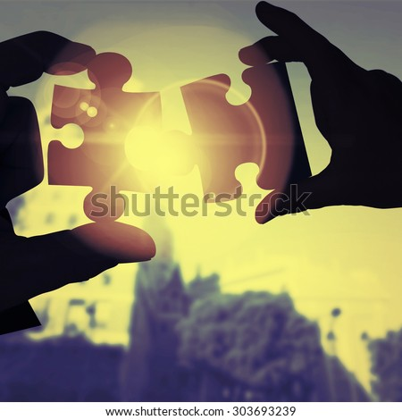 Mid section of a businessman in suit with hands out against jigsaw - stock photo
