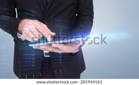 Mid section of a businessman touching digital tablet against grey vignette - stock photo