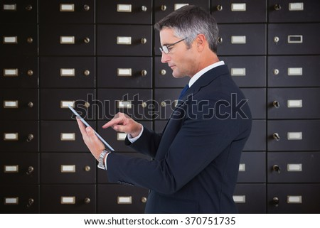 Mid section of a businessman touching tablet against wall of black lockers