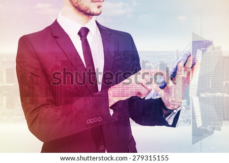Mid section of a businessman using digital tablet pc against room with large window looking on city - stock photo
