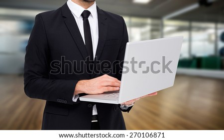 Mid section of a businessman using laptop against fitness studio - stock photo