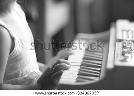 Mid section of a girl playing the piano