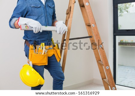 Mid section of a handyman with tool belt around his waist and hard hat - stock photo