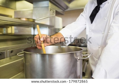 Mid section of a male chef preparing food in the kitchen