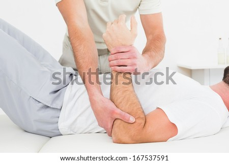 Mid section of a male physiotherapist examining a young man's hand in the medical office