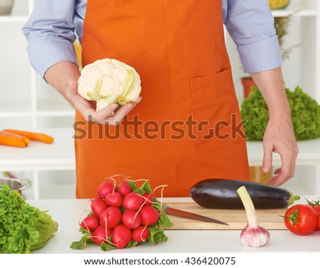 Mid section of a man preparing to chop cauliflower in the kitchen at home.