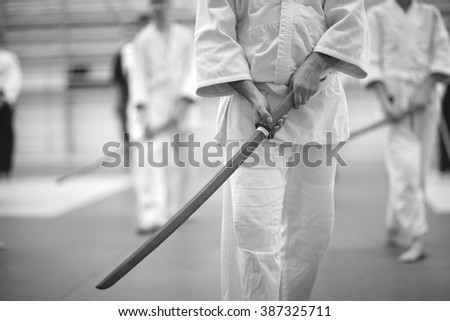 Mid section of a man standing in white kimono with wooden sword in hands, aikido concept - stock photo