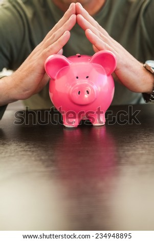 Mid section of a man with joined hands on piggy bank at home in the living room - stock photo