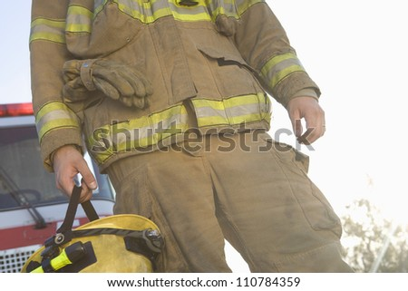 Mid section of a middle aged firefighter standing with fire brigade in the background - stock photo
