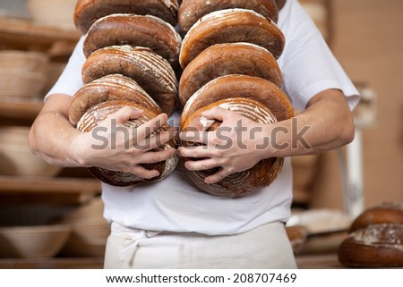 mid section of a worker carrying bread in bakery kitchen - stock photo
