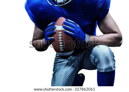 Mid section of American football player kneeling while holding ball against black background - stock photo