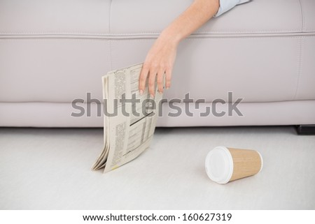 Mid section of an asleep woman holding newspaper on sofa at home - stock photo