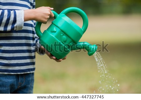 Mid section of boy pouring water from watering can in park