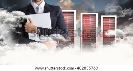 Mid section of businessman holding computer against blue and orange sky with clouds - stock photo