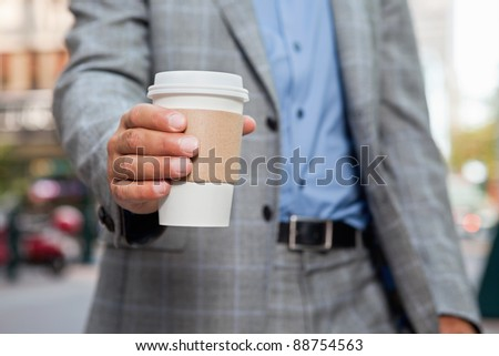 Mid section of businessman holding disposable coffee cup - stock photo