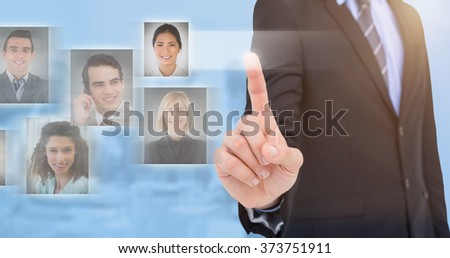 Mid section of businessman pointing something up against blue background - stock photo