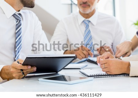 Mid section of businessmen and businesswomen discussing at his desk in the office - stock photo