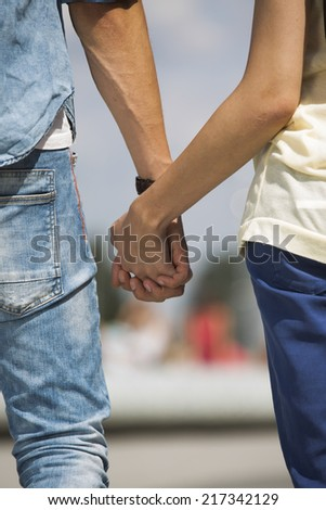Mid section of couple holding hands outdoors
