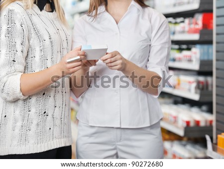 Mid-section of female pharmacist advising customer how to take medicine - stock photo