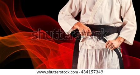 Mid section of fighter tightening karate belt against black background