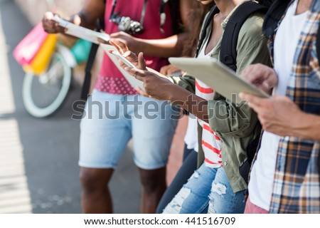 Mid section of friends using digital tablet and mobile phone - stock photo