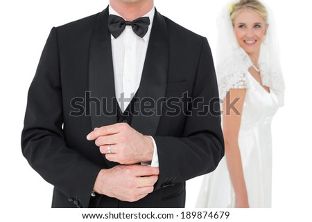 Mid section of groom adjusting tuxedo sleeve while bride looking at him over white background