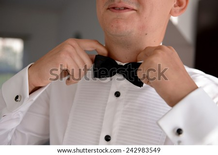 Mid section of happy groom adjusting his bow tie - stock photo
