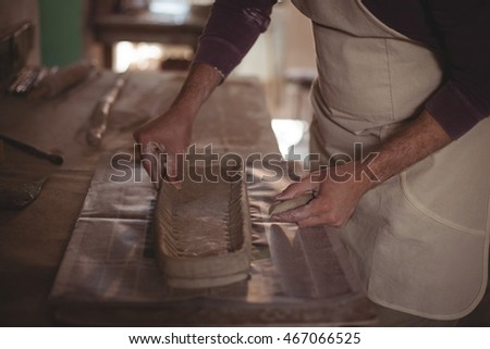 Mid section of male potter designing clay in pottery workshop